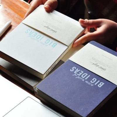 Hand Holding Light Blue Big Ideas Hardcover Notebook Next To Dark Blue Option