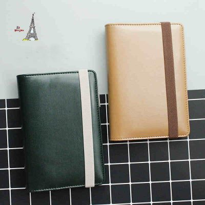 Green and beige faux leather refillable journal with strap closure flatlay