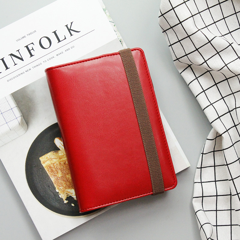 Red faux leather refillable journal with brown strap closure flatlay