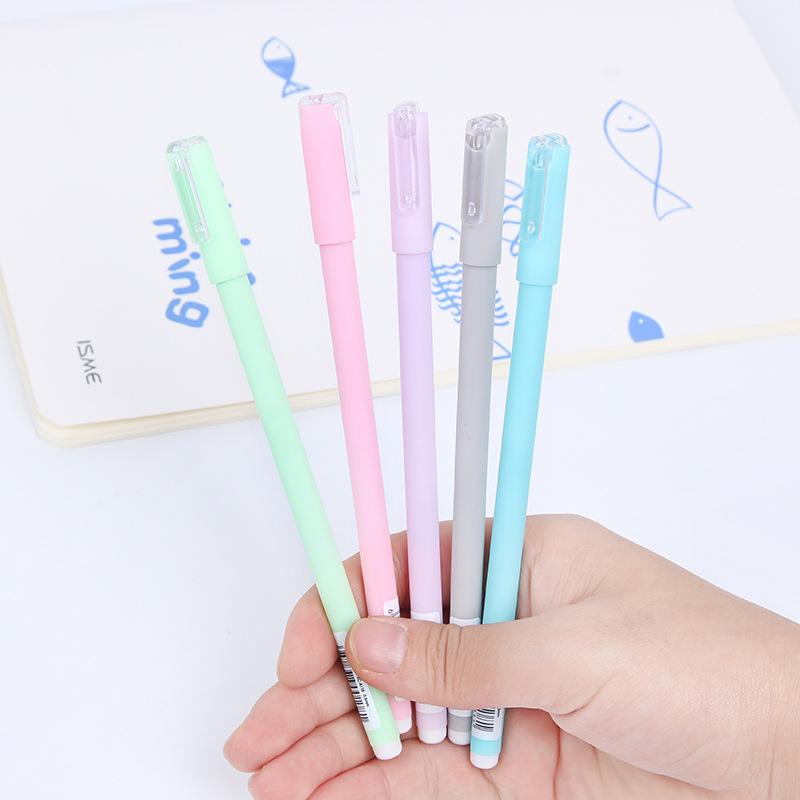 Hand holding green pink purple grey blue pastel gel pens