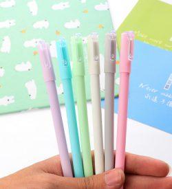 Hand holding 6 different color pastel gel pens