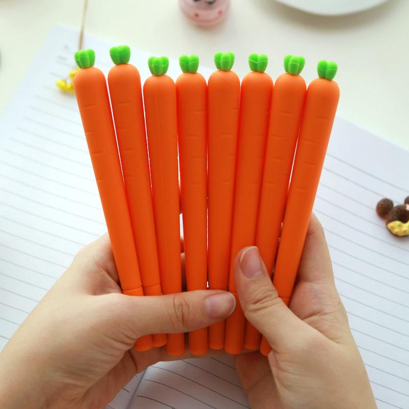 Hands holding 8 carrot gel pens