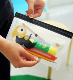 Hand holding and zipping smiley mustache flat pencil case with stationery