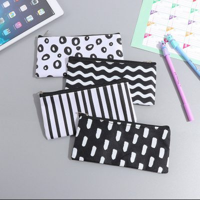 Black and white flat pencil case flatlay dash stripes waves circles designs