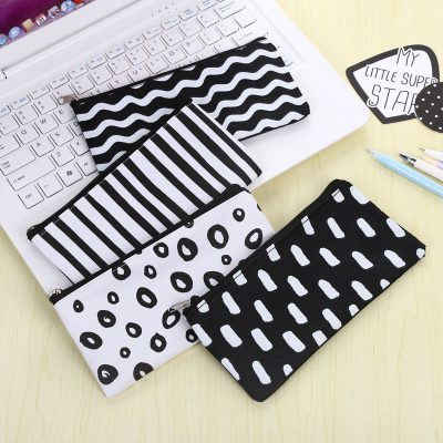 Black and white flat pencil case 4 design options flatlay with laptop and pens