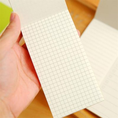 Closeup of hand holding kraft memo pad with grid paper