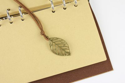 Faux leather leaf refillable journal with charm and kraft paper notebook pages closeup