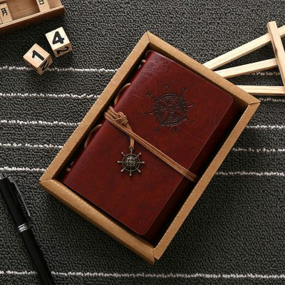 Brown faux leather nautical journal notebook with ship wheel charm inside box