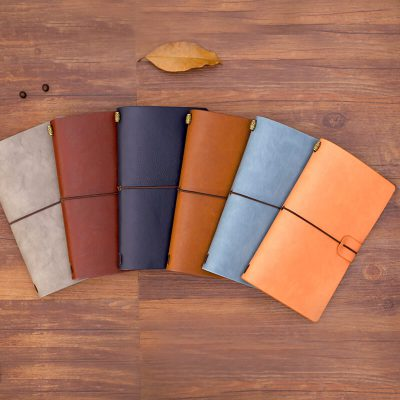 Faux leather refillable journal six notebooks brown blue orange on table