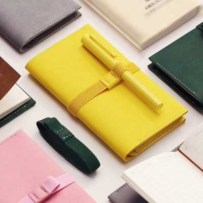 Faux leather refillable notebook organizer with yellow pen holder and pen flat lay