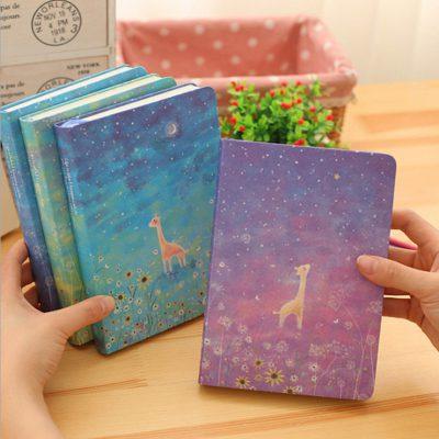 Hand holding Starry Night Giraffe Notebooks