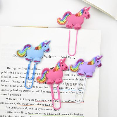 4 Rainbow Unicorn Paperclips On Top Of Book