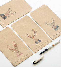 Deer Kraft Paper Envelopes Flatlay Next To Uncapped Pen