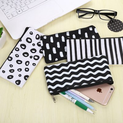 Black and white flat pencil case 4 design options flatlay with laptop pens iphone glasses