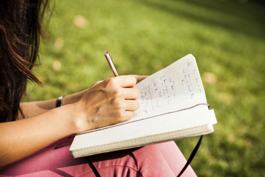 College student writing in a journal